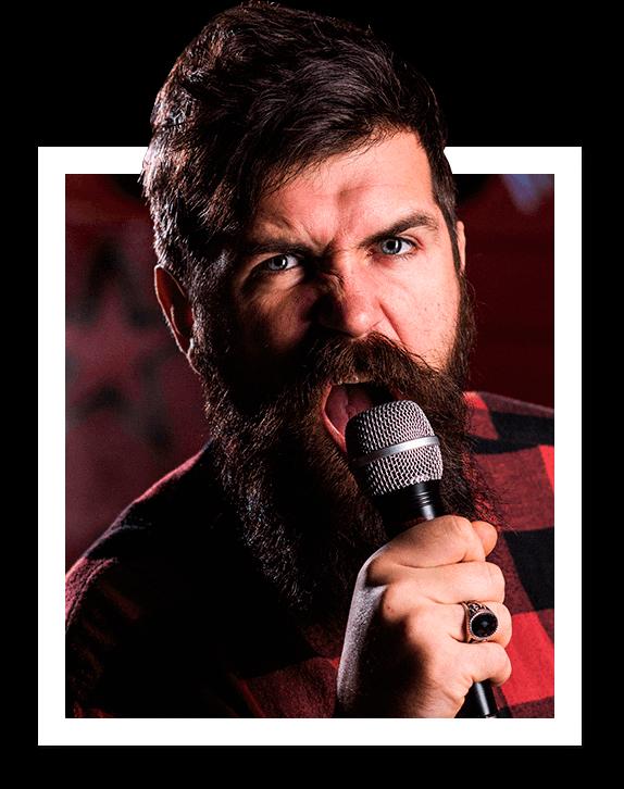 Homem barbudo de camisa xadrez cantando com microfone na mão
